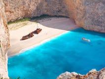 Vista bonita em turistas sightseeing da natação do barco do curso da praia do naufrágio na água azul do mar Ionian próximo às cav Foto de Stock