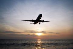 A vista bonita em um mar com plano em um céu durante um por do sol colorido fotos de stock
