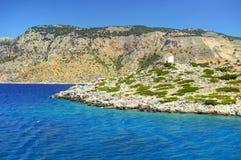 A vista bonita na pedra da ilha de Symi balança o flouring-moinho branco do moinho com o telhado alaranjado no monte verde Água c Imagem de Stock Royalty Free