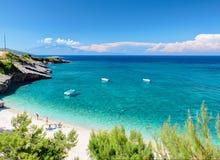 A vista bonita na pedra de Zakynthos e a areia encalham, as rochas de pedra, natação e brindando os povos na areia branca encalha Foto de Stock
