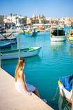 Vista bonita nos barcos coloridos eyed tradicionais Luzzu no porto da aldeia piscatória mediterrânea Marsaxlokk, Malta fotografia de stock royalty free
