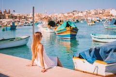 Vista bonita nos barcos coloridos eyed tradicionais Luzzu no porto da aldeia piscatória mediterrânea Marsaxlokk, Malta imagem de stock