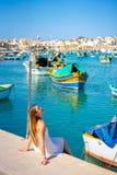 Vista bonita nos barcos coloridos eyed tradicionais Luzzu no porto da aldeia piscatória mediterrânea Marsaxlokk, Malta fotografia de stock