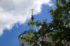 Vista borrada da igreja ortodoxa dourada da cruz e do russo no fundo do céu azul e das nuvens, Bolshaya Halan Foto de Stock Royalty Free