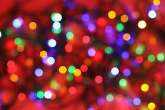 Vista borrosa de las luces de la Navidad que brillan intensamente en fondo del color imágenes de archivo libres de regalías