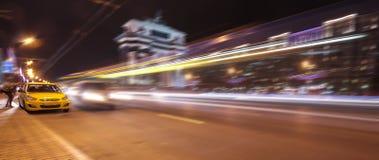 Vista borrosa del taxi amarillo que toma a una muchacha del pasajero en una avenida grande con las vías largas de autobuses y de  foto de archivo libre de regalías