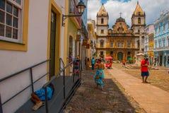 Vista brilhante de Pelourinho em Salvador, Brasil, dominado pela grande cruz de pedra colonial de Cruzeiro de Sao Francisco Chris imagem de stock royalty free