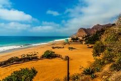 Vista cênico bonita em uma praia solitária com uma cabine da salva-vidas imagens de stock