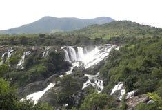 Vista cênico da cachoeira com árvores e as montanhas verdes no fundo Fotografia de Stock