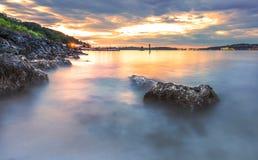 A vista cênico da rocha na praia de Alki na noite com reflete Fotos de Stock Royalty Free