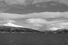 A vista cênico da viagem do barco em fiordes nevado bonitos repica no mar norueguês em preto e branco com nuvens, Noruega Fotografia de Stock