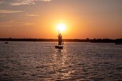 Vista cênico de um veleiro pequeno em um por do sol em um porto da cidade imagem de stock
