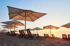 Vista cênico do Sandy Beach com as camas do sol no mar e as montanhas no por do sol Amara Dols Vita Luxury Hotel recurso Fotos de Stock Royalty Free