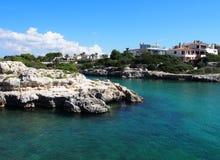 Vista cênico do santandria de cala no menorca com o mar ensolarado brilhante cercado pelos penhascos e pelas casas brancas que ne fotos de stock royalty free