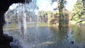 Vista cênico fora da caverna ao lago waterfall no movimento lento do Madri do parque de Buen Retiro video estoque