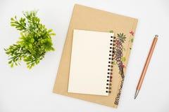 Vista-caderno superior com o lápis da cor na tabela branca fotografia de stock royalty free