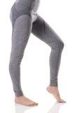 Vista calda delle gambe sexy della donna di misura dal lato in biancheria intima termica di sport grigi con il modello Fotografie Stock