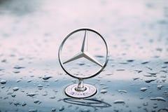 Vista cercana de la estrella Logo Of Mercedes Benz At Hood Of Blue mojado del metal Imagen de archivo