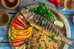 Vista cercana de la lubina asada a la parrilla con las verduras y el ptitim, cocina de Oriente Medio foto de archivo libre de regalías