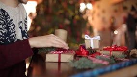Vista cercana de las manos del hombre que atan un arco en regalos para la Navidad Actuales cajas de embalaje masculinas en el pap metrajes