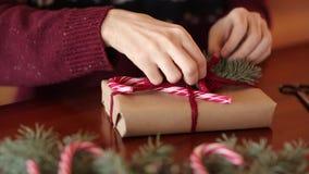 Vista cercana de las manos del hombre que atan un arco en regalos para la Navidad Actuales cajas de embalaje masculinas en el pap almacen de video