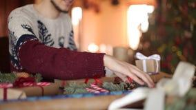 Vista cercana de las manos del hombre que atan un arco en regalos para la Navidad Actuales cajas de embalaje masculinas en el pap almacen de metraje de vídeo