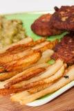 Vista cercana de patatas fritas con las albóndigas y los guisantes Fotografía de archivo libre de regalías