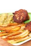 Vista cercana de patatas fritas con las albóndigas y los guisantes Fotos de archivo libres de regalías