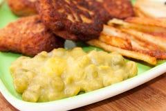 Vista cercana de patatas fritas con las albóndigas y los guisantes Imagen de archivo libre de regalías