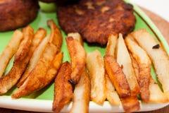 Vista cercana de patatas fritas con las albóndigas y los guisantes Foto de archivo libre de regalías