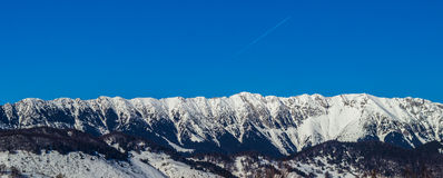 Vista cercana del canto iluminado por el sol de las montañas de Bucegi con las cuestas escarpadas cubiertas por la nieve en la sa Fotos de archivo