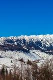 Vista cercana del canto iluminado por el sol de las montañas de Bucegi con las cuestas escarpadas cubiertas por la nieve en la sa Fotografía de archivo libre de regalías
