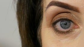 Vista cercana del ojo azul de la mujer adulta de mediana edad con maquillaje hermoso en un salón de belleza almacen de metraje de vídeo