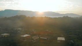 Vista cinemática aérea de los pueblos del país y de las montañas del Cáucaso durante mañana brumosa del verano en la salida del s almacen de metraje de vídeo
