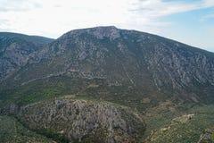 Vista circostante del paesaggio fresco della valle della montagna del calcare di Parnassus, oliveti verdi con il fondo luminoso d fotografie stock