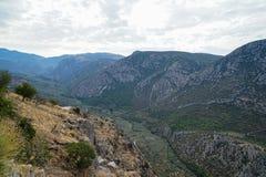 Vista circostante fresca della valle della montagna del calcare di Parnassus, delle tonalità degli oliveti verdi e di altri alber fotografia stock