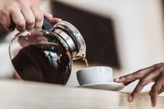 vista colhida do café de derramamento do garçom no copo no café fotografia de stock