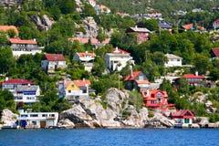 Casas e cabanas na costa e nos montes do fiorde de Bergen. Imagens de Stock Royalty Free