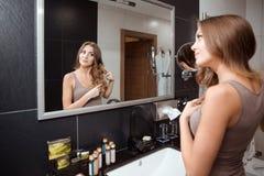 Vista consideravelmente fêmea no espelho ao escovar o cabelo imagem de stock royalty free