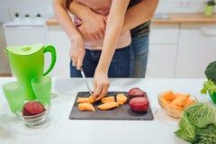 Vista cosechada de las manos de la mujer que cortan verduras org?nicas Familia de amor del vegano que cocina verduras en la cocin fotos de archivo