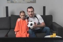 Vista cosechada del partido de fútbol de observación de la hija y del padre en camisetas de las fans fotografía de archivo