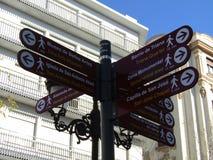 Vista cruzada del poste indicador del camino Paisaje urbano de Sevilla fotografía de archivo