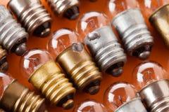 Vista d'annata di macro delle lampade Le lampadine con il bronzo e l'argento strutturati dell'oro sorgono Fondo arancio, profondi Immagini Stock Libere da Diritti