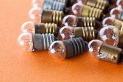 Vista d'annata di macro delle lampade Le lampadine con il bronzo e l'argento strutturati dell'oro sorgono Fondo arancio, macro vi Immagine Stock Libera da Diritti