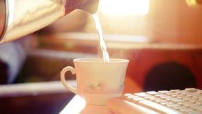 A vista da água quente que derrama no copo ou na caneca quente de café ou de chá, com vapor do vapor borrou o fundo 1920x1080 video estoque