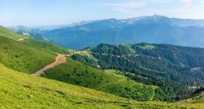 A vista da altura de um vale verde da montanha com as construções residenciais cercadas por montanhas altas neve-tampado foto de stock