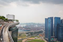 Vista da associação da infinidade no auge de Marina Bay Sands Hotel com guindastes e contentores do porto no fundo em Singapura imagens de stock royalty free