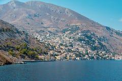 Vista da baía bonita com as casas coloridas no montanhês da ilha de Symi imagem de stock royalty free