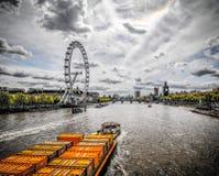 Vista da barca que puxa cointainers amarelos ao longo do rio Tamisa Londres fotografia de stock