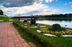 Vista da cama de flor do beira-rio no parque da cidade e da ponte velha no fundo, cidade de Volga de Tver, Rússia Fotografia de Stock Royalty Free